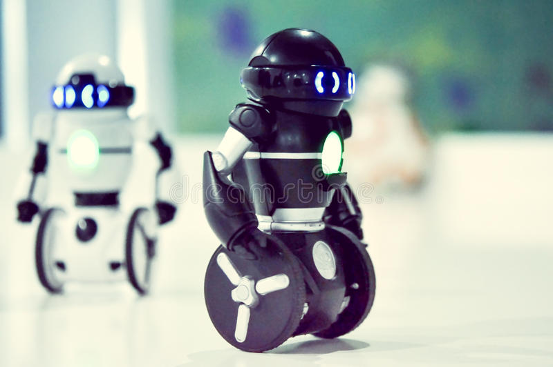 Small robots, humanoid with small wheels instead of legs and luminous eyes. royalty free stock image