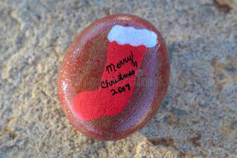 Small rock painted red with Christmas stocking and Merry Christmas 2017. A small rock with a red Christmas stocking painted on it and the words Merry Christmas royalty free stock photos