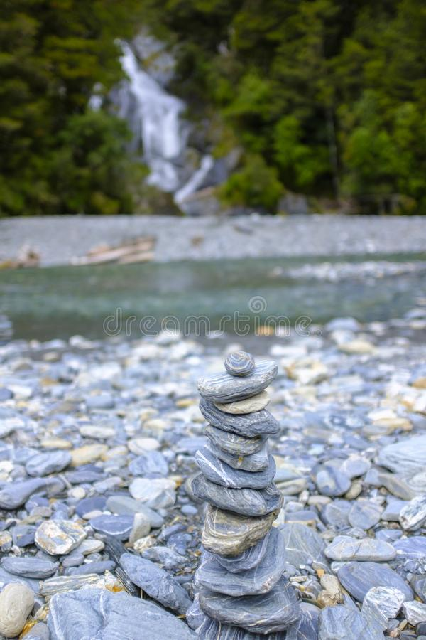 Small rock pile next to a river. Small rock pile with a river in the background stock photo