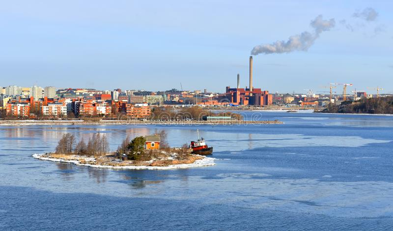 Small rocky island of Helsinki archipelago against backdrop of industrial area of city. Suomi royalty free stock images