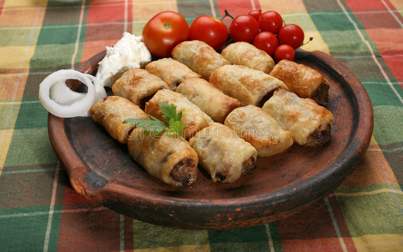 Small rolled pies. Small rolled meat pies on clay plate royalty free stock photo