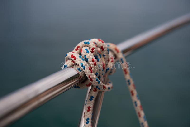 Small rope knot tied around silver metal rod. Close up of a knot stock photo