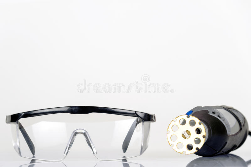 Small rotary tool with saw attachment and safety spectacles isolated. Small rotary tool with saw attachment and safety spectacles, isolated royalty free stock image
