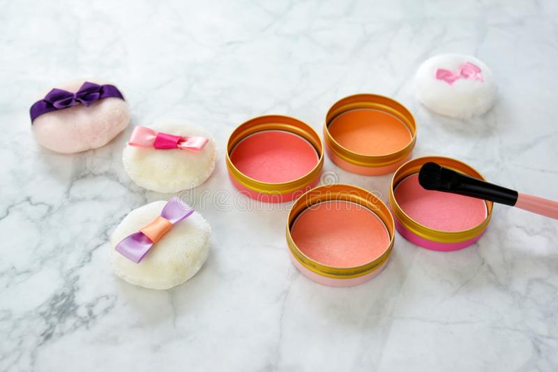 Small round blusher pots with different shades of pink, cute powder puffs with ribbons and makeup brush stock photography
