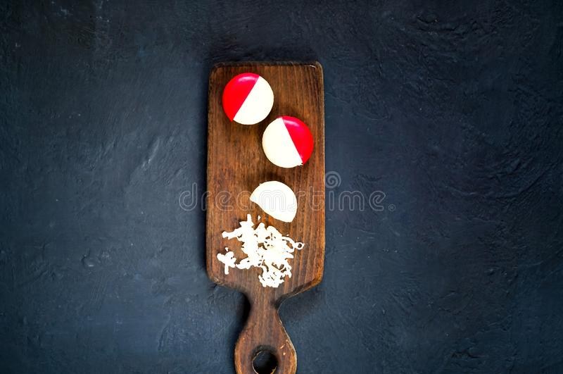 Small round cheese in paraffin pack on wooden board on dark blue background, copy space stock photography