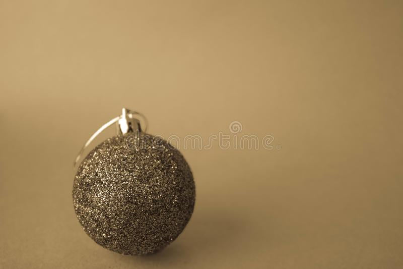 Small round xmas festive New Year`s ball, Christmas toy pasted over with sparkles on a yellow retro sepia background royalty free stock photos