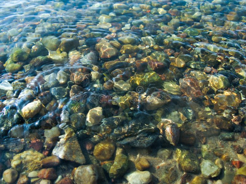 Small round stones under clear clear water royalty free stock image