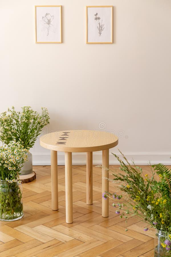 A small round wooden table surrounded by fresh meadow flowers standing on a parquet against a light beige wall with illustrations royalty free stock image