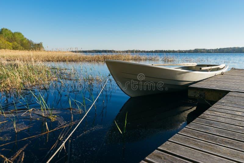 Small row boat moored at the pier by springtime morning. Saadjarv lake, Estonia stock photography