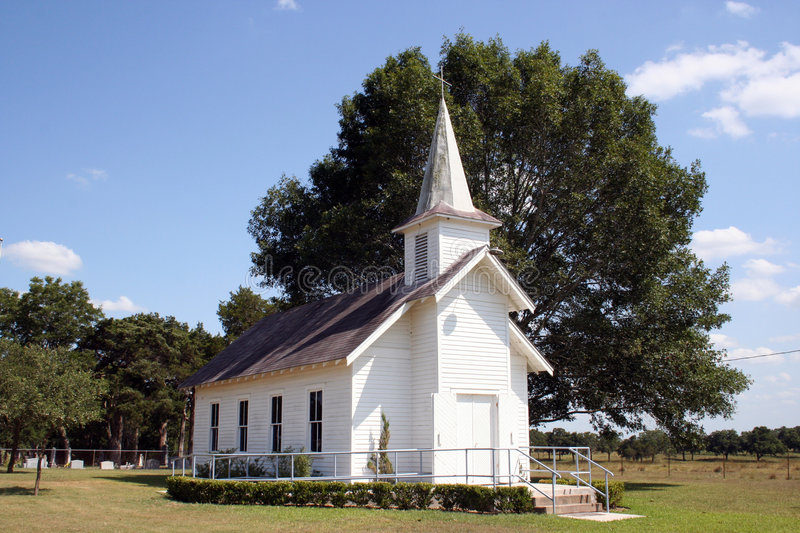 Small Rural Church in Texas. A small rural church in Texas. There is a cemetary and a large oak tree behind the church royalty free stock images