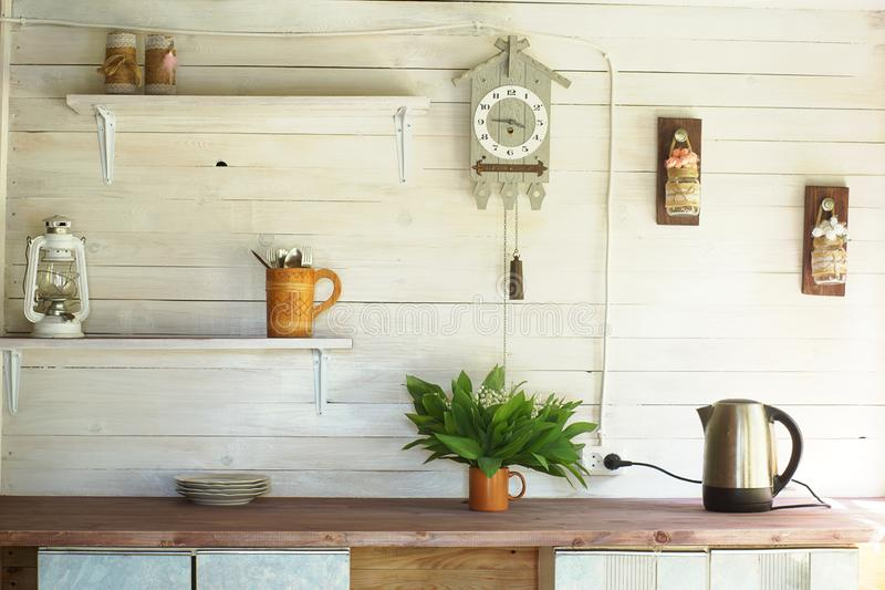 Small rustic kitchen with a clock on the wall, white plank walls and wooden shelves royalty free stock images