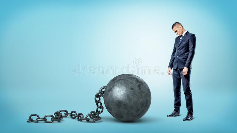 A small sad businessman looking down to a giant iron ball and chain on blue background. royalty free stock images