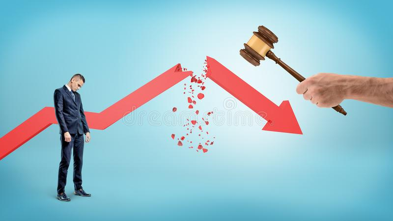 A small sad businessman stands near a red statistic arrow broken by a giant hand holding a judge gavel. royalty free stock images