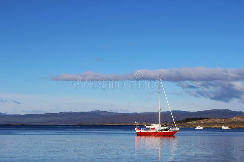 Small sailing boat on calm waters. royalty free stock images