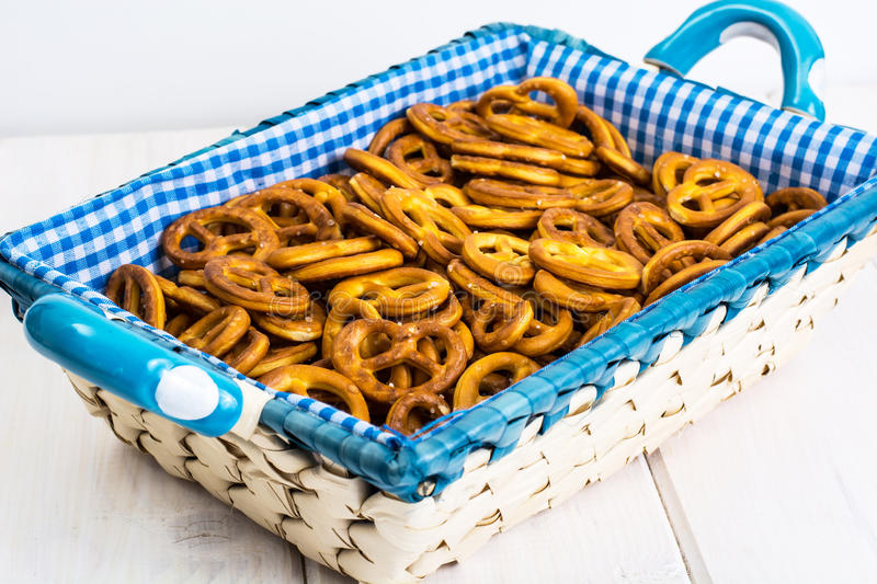 Small salted pretzels cookies in a basket on a white wooden table stock image