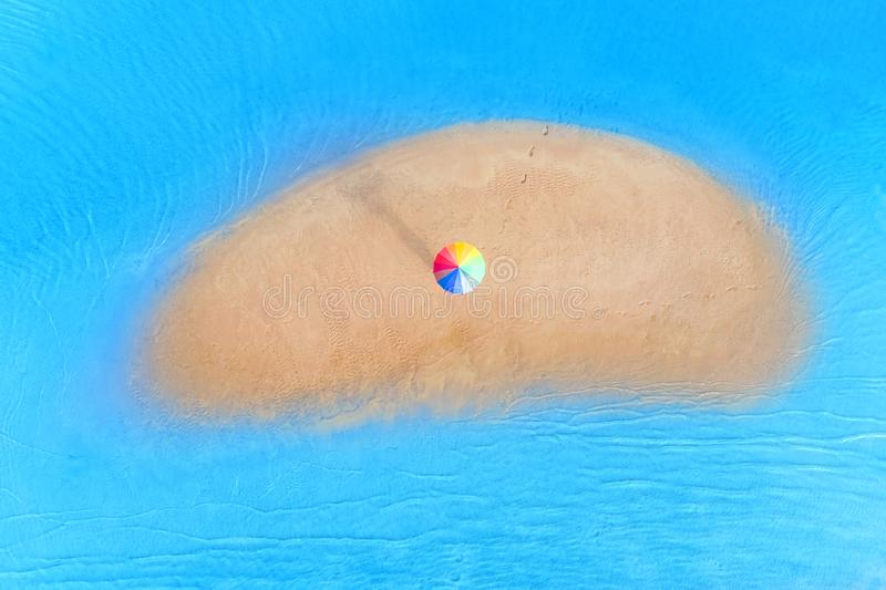Small sandy island with someone under rainbow colored umbrella on it. Top aerial view royalty free stock photography