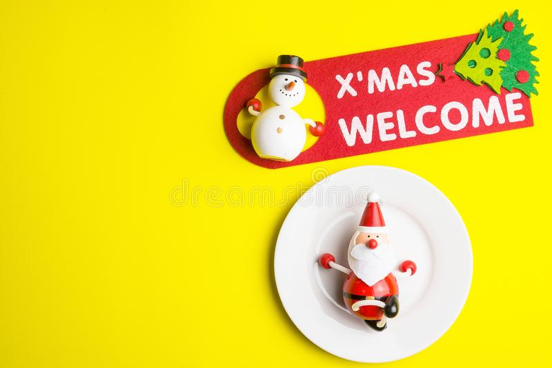 Small Santa Claus on white dish isolated on yellow background at. Christmas day.Theme Christmas day background royalty free stock photography