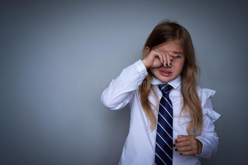 Small schoolgirl covering face, crying portrait stock photography