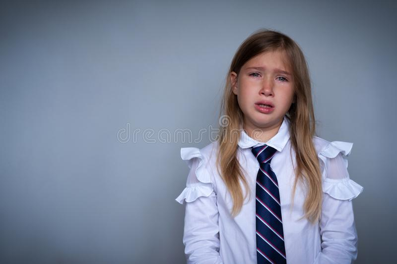 Small schoolgirl covering face, crying portrait stock photo