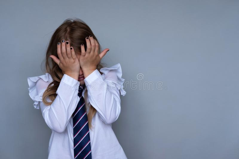 Small schoolgirl covering face, crying portrait stock image
