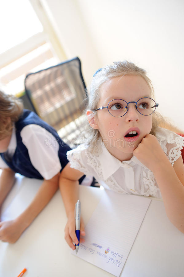 Small schoolgirl of an elementary school sits at a desk in thoughtfulness. Small schoolgirl of an elementary school sits at a school desk in thoughtfulness royalty free stock photography
