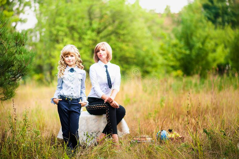 A small schoolgirl and a grown-up graduate in school uniform are holding an apple against the backdrop of a green forest. stock photography