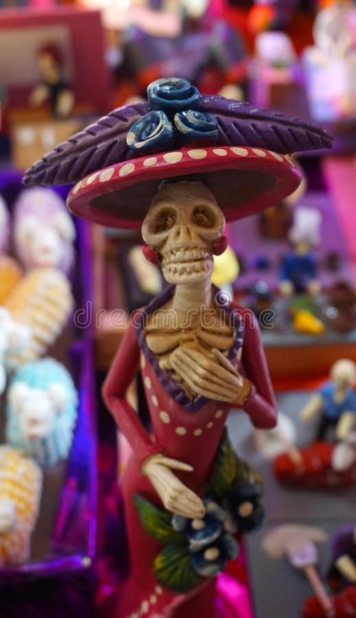 Mexican catrina. Small sculpture of a traditional mexican catrina, wearing a long pink dress with a long hat decorated with flowers, mexican traditional royalty free stock photography