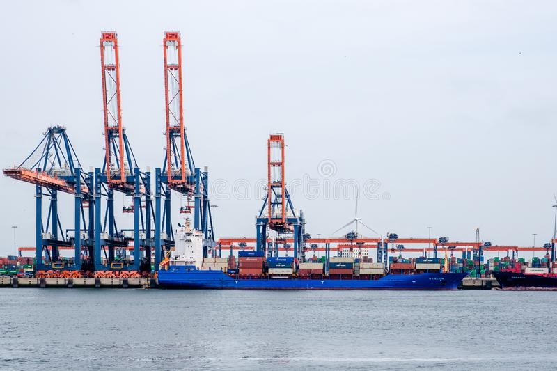 Small sea container ship in a container terminal in the port of Rotterdam stock photo