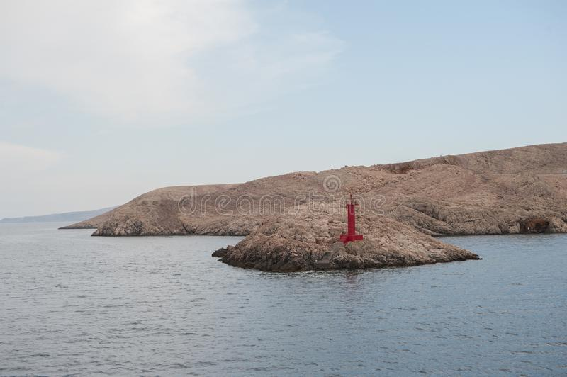 Small sea red light signal, lighthouse in island Pag, Croatia. Adriatic sea. royalty free stock images