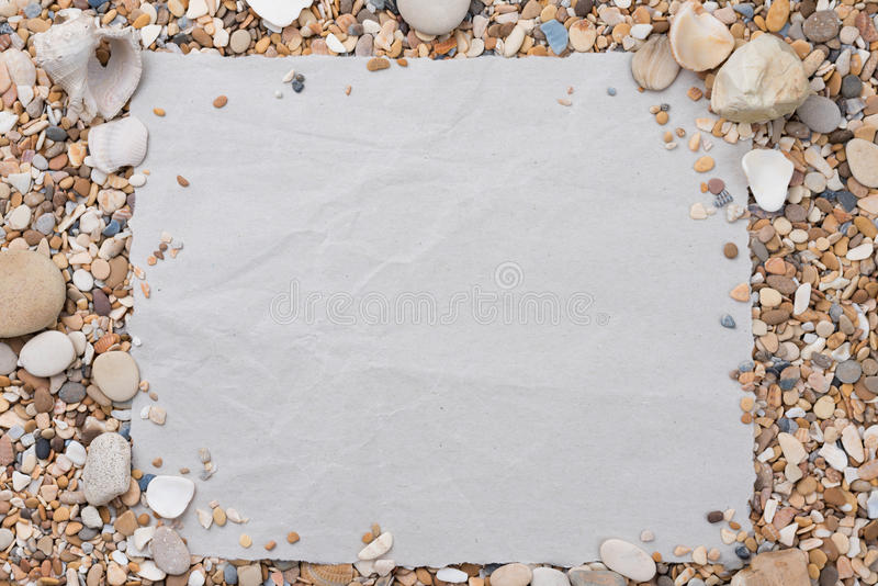 Small sea stones and shells, on a textured paper, with a free space under the text, title, ad, menu or picture. Small sea stones and shells, on a textured paper royalty free stock photos