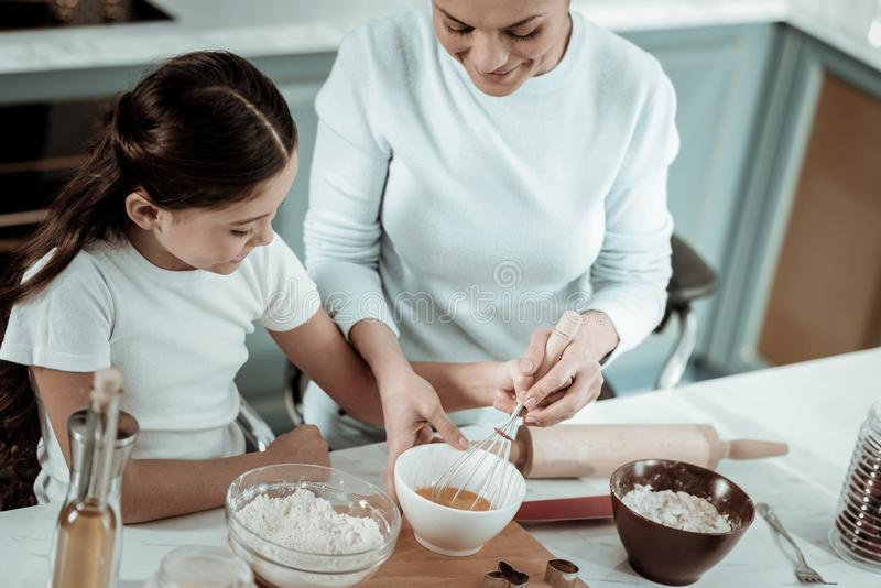 Careful mother opening cooking secrets to the daughter royalty free stock photo
