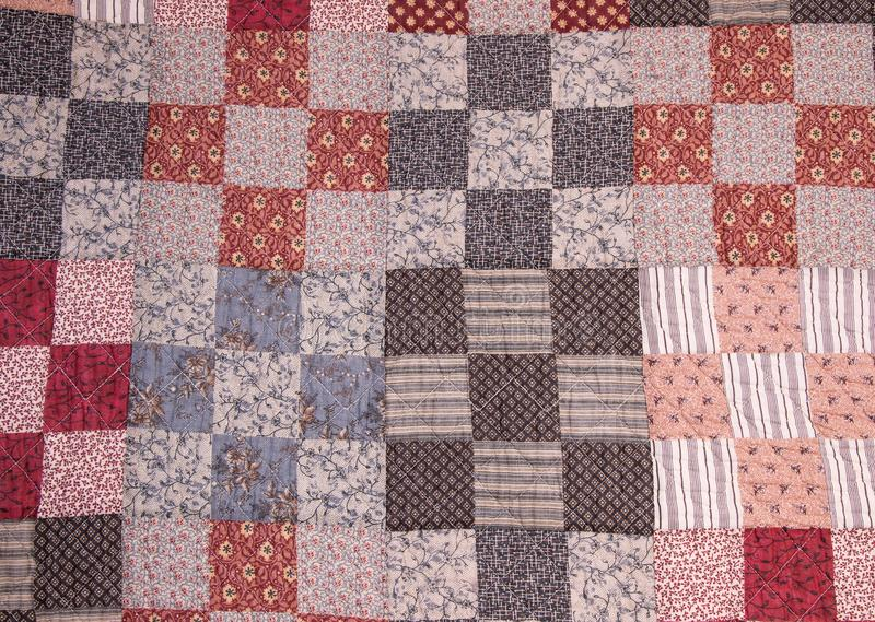 A handmade quilt pattern of small squares with a variety of patterns and colors. royalty free stock photo