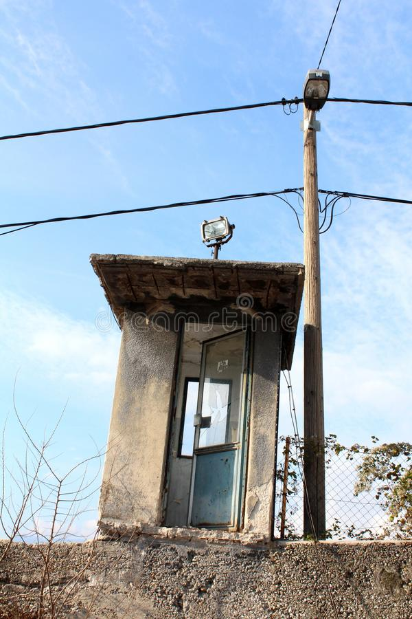 Small security guard structure with metal doors and broken window next to concrete electrical utility pole with mounted street stock photography