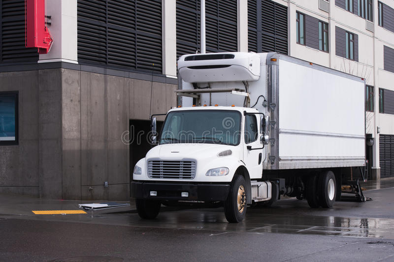 Small semi truck with reefer unit on box trailer for local delivery unloading delivered food. Modern white semi truck of middle duty and size with day cab and stock photo