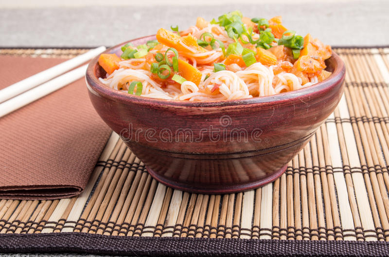 Small serving of rice vermicelli hu-teu with vegetables. Small serving of rice vermicelli hu-teu with vegetable carrot sauce in a small brown wooden bowl on a stock photography