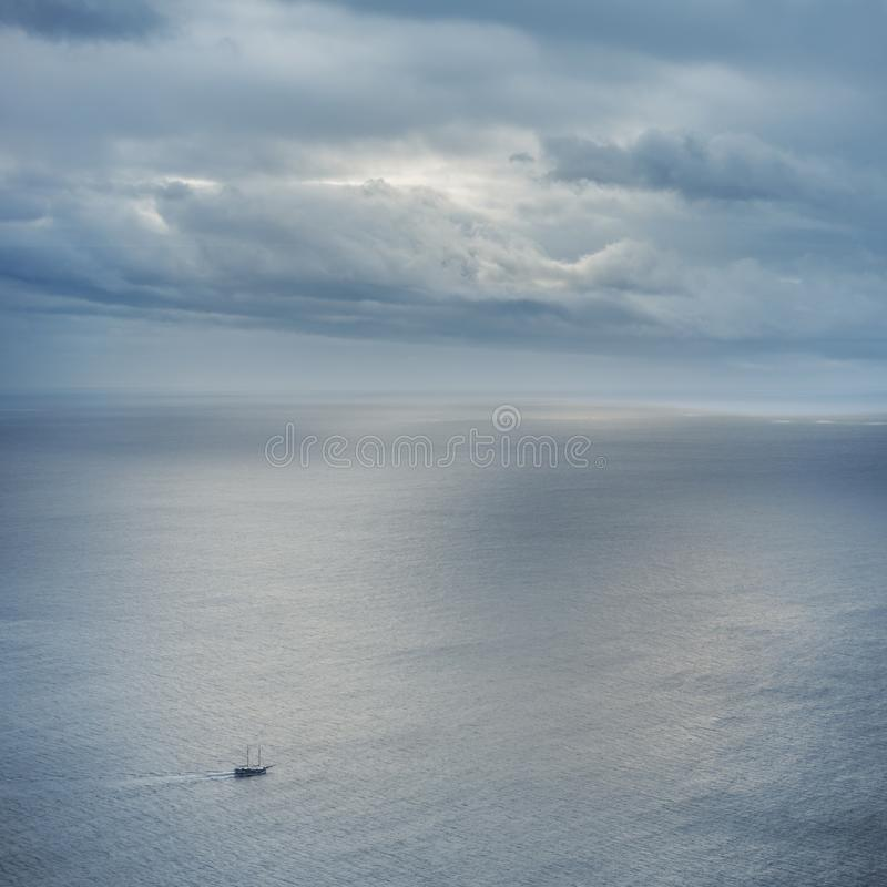 Small ship on big ocean. With clouds and beautiful light royalty free stock images