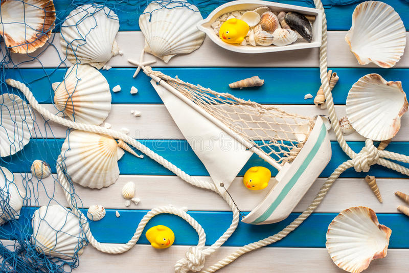 Small Ship, fishing boat, shells and sailor rope on a wooden background. Sea concept. Yellow rubber duck. royalty free stock photos