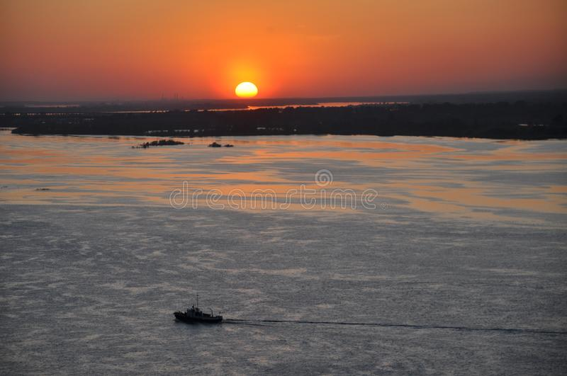 A small ship floats on the river lit by the rays of the setting sun. Water royalty free stock photo