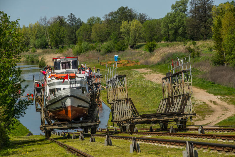 Small ship swimming on land. Small tourist ship after docking driving on a carriage to higher level through Elblag-Ostroda Canal in northern Poland. Area of royalty free stock images