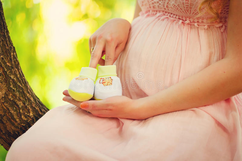 Small shoes for the unborn baby. In the belly of pregnant woman royalty free stock photography