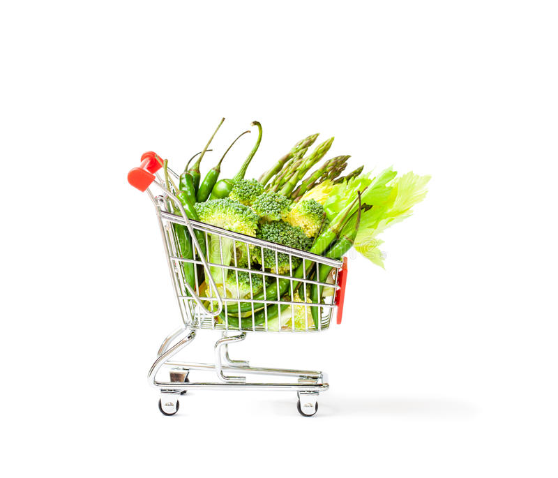 Small shopping cart full of green healthy vegetables royalty free stock image
