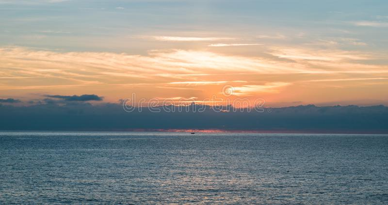Nice cloudy sunrise scene. Small silhouette of a boat in nice cloudy sunrise scene royalty free stock image