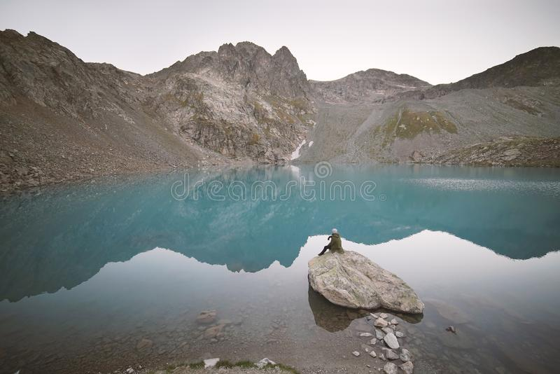 Small silhouette of traveler staring at the lake. stock photos