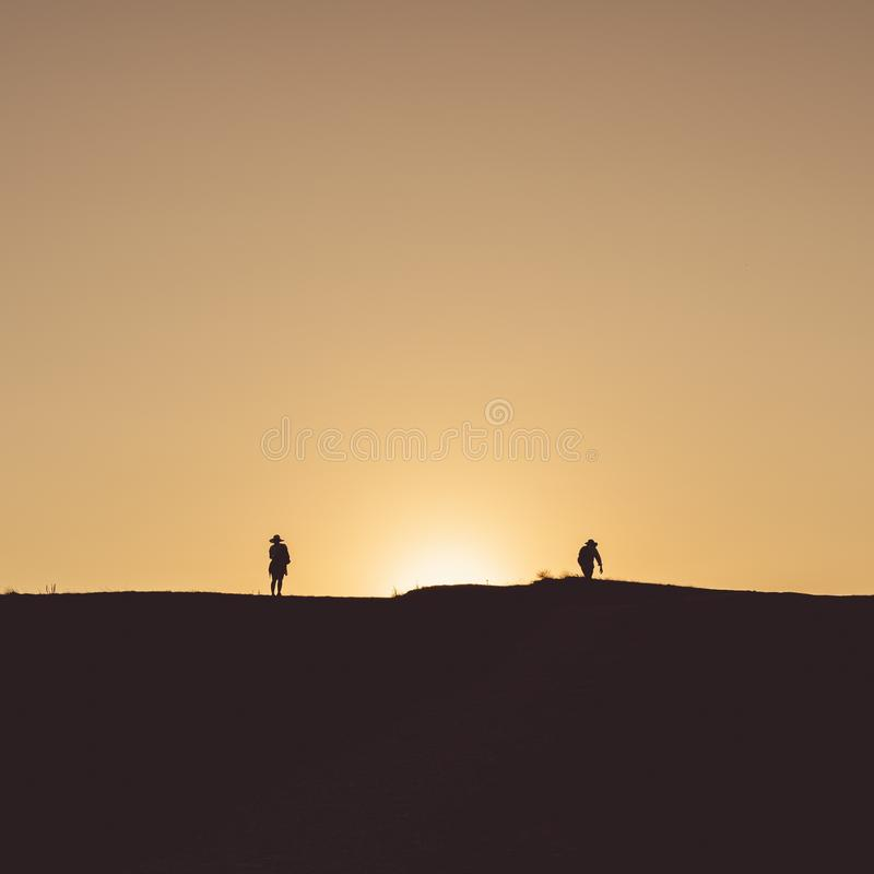 Small silhouettes of people walking on the land with with the yellow sunset sky in the background. The small silhouettes of people walking on the land with with royalty free stock photo