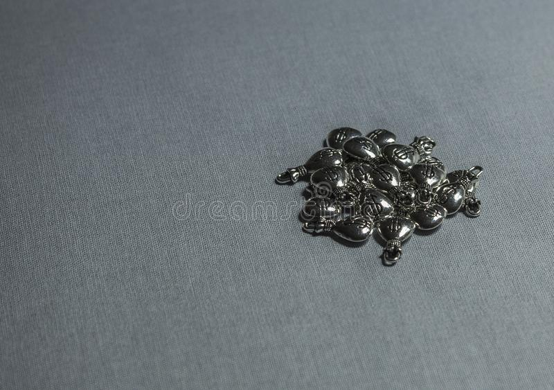 Small silver ornaments. jewelry. on gray background stock photos