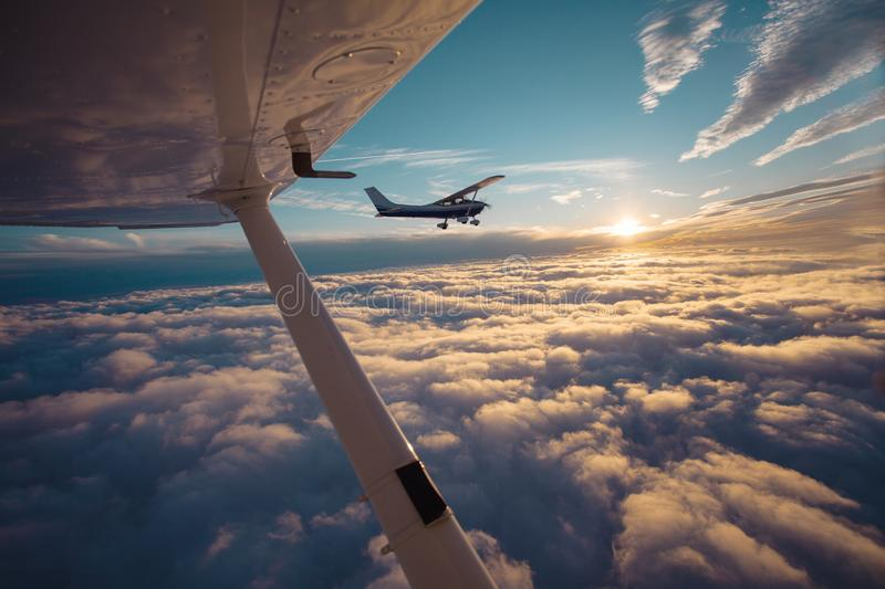 Small single engine airplane flying in the gorgeous sunset sky through the sea of clouds stock photography