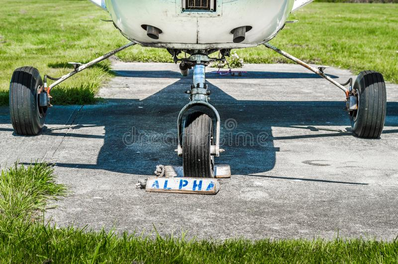 Small single engine airplane wheels and landing gear on parking pad with wheel chocks. stock image