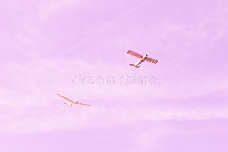 Small single-engine old vintage plane and glider flying against the pink sky, concept of teamwork, dream, happy future and. Positive outlook on life royalty free stock image
