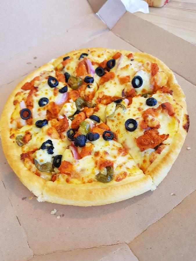 Small size pizza with chicken cheese and black olives food. Small size pizza with chicken cheese and black olives stock images