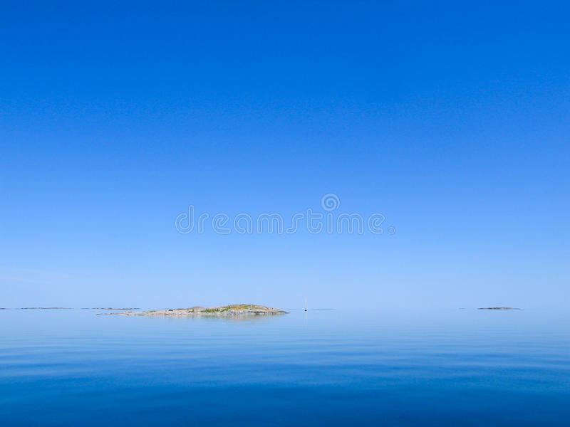 Small skerry in very calm sea. A small skerry or island in a very calm sea. A sailingboat at distance is trying to get some wind to pass by. Stockholm royalty free stock image
